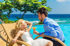 Happy bride and groom enjoy a cocktail poolside infinity. Tropic Stock Photo
