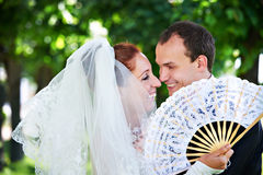Happy bride and groom with fan Stock Images