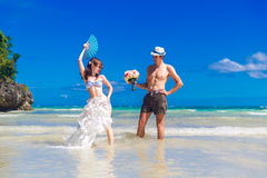 Happy bride and groom with a fan and a wedding bouquet having fu Royalty Free Stock Photo