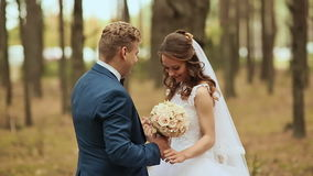 Happy bride and groom in the forest. Touching hands. The groom embraces the bride with a bouquet. Tears of happiness. Happy bride and groom in the forest stock footage