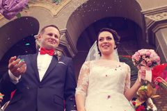Happy bride and groom in front of church Royalty Free Stock Photo
