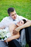 Happy bride and groom on grass Royalty Free Stock Image