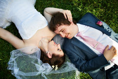 Happy bride and groom on grass Royalty Free Stock Images