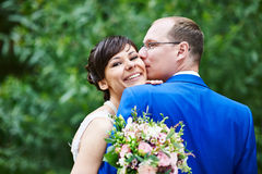 Happy bride and groom on grass at wedding walk Stock Image