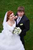 Happy bride and groom on green background Royalty Free Stock Images