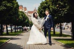 Happy bride and groom in green city alley on wedding walk Stock Photos