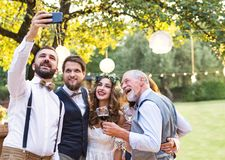 Bride, groom and guests with smartphone taking selfie outside at wedding reception. Happy bride, groom and guests with smartphone taking selfie outside at stock photography