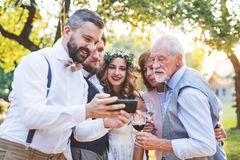 Bride, groom and guests with smartphones taking selfie outside at wedding reception. Happy bride, groom and guests with smartphones taking selfie outside at royalty free stock photos