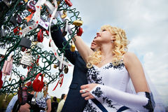Happy bride and groom hanging padlock Royalty Free Stock Images