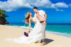 Happy bride and groom having fun on a tropical beach Stock Photography