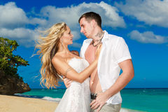 Happy bride and groom having fun on a tropical beach Royalty Free Stock Photos