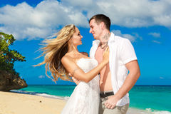 Happy bride and groom having fun on a tropical beach Stock Photo