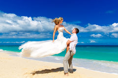 Happy bride and groom having fun on a tropical beach Stock Image