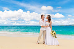 Happy bride and groom having fun on a tropical beach Royalty Free Stock Images