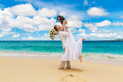 Happy bride and groom having fun on a tropical beach Royalty Free Stock Image