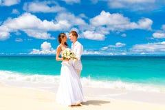 Happy bride and groom having fun on a tropical beach Stock Photo