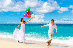 Happy bride and groom having fun on a tropical beach Royalty Free Stock Photo