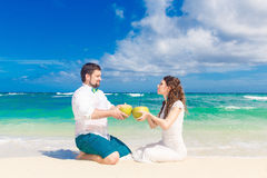 Happy bride and groom having fun on a tropical beach with coconuts Stock Images