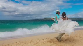 Happy bride and groom having fun on a tropical beach. Just marri stock footage
