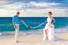 Happy bride and groom having fun on a tropical beach. Just marri Stock Photos