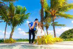 Happy bride and groom having fun on a tropical beach under the p Stock Image