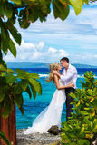 Happy bride and groom having fun on a tropical beach under the p Stock Photo