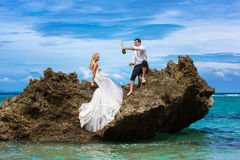 Happy bride and groom having fun on a tropical beach under the p Stock Photography