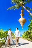 Happy bride and groom having fun on a tropical beach under the p Royalty Free Stock Image