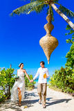 Happy bride and groom having fun on a tropical beach under the p Royalty Free Stock Images
