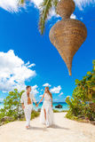 Happy bride and groom having fun on a tropical beach under the p Stock Photos