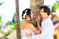 Happy bride and groom having fun on a tropical beach under the p Royalty Free Stock Photos