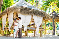 Happy bride and groom having fun on a tropical beach under the p Stock Images