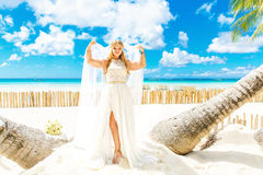 Happy Bride and Groom having fun on the tropical beach under the Royalty Free Stock Photo