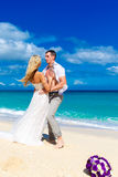 Happy bride and groom having fun on a tropical beach. wedding bo. Uquet in the foreground Royalty Free Stock Photography