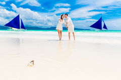 Happy Bride and Groom having fun on the tropical beach. Wedding. And honeymoon concept Stock Photos