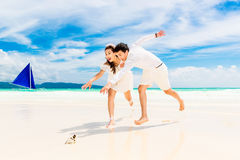 Happy Bride and Groom having fun on the tropical beach. Wedding Royalty Free Stock Images