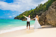 Happy Bride and Groom having fun on the tropical beach. Wedding. And honeymoon concept Stock Images