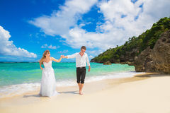 Happy Bride and Groom having fun on the tropical beach. Wedding. And honeymoon concept Royalty Free Stock Photo