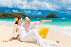 Happy bride and groom having fun on a tropical beach. Wedding an Stock Photos
