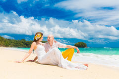 Happy bride and groom having fun on a tropical beach. Wedding an Stock Images