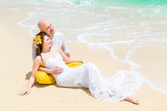 Happy bride and groom having fun on a tropical beach. Wedding an Royalty Free Stock Image