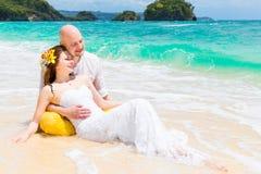Happy bride and groom having fun on a tropical beach. Wedding an Royalty Free Stock Photo