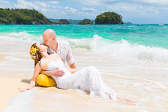 Happy bride and groom having fun on a tropical beach. Wedding an Stock Photography