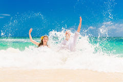 Happy bride and groom having fun on a tropical beach. Wedding an Royalty Free Stock Images