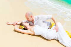 Happy bride and groom having fun on a tropical beach. Wedding an Stock Photography