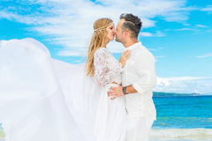Happy bride and groom having fun on a tropical beach. Wedding an. D honeymoon on the tropical island Royalty Free Stock Images
