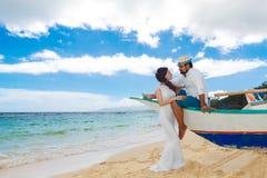 Happy bride and groom having fun on a tropical beach. Wedding an. D honeymoon on the tropical island Stock Images