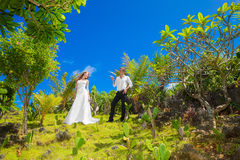 Happy bride and groom having fun on a tropical garden under the Royalty Free Stock Photos
