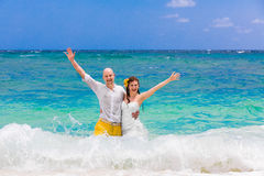 Happy bride and groom having fun in the waves on a tropical beac Royalty Free Stock Image