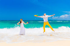 Happy bride and groom having fun in the waves on a tropical beac Royalty Free Stock Photos